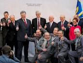 Ukrainian President Petro Poroshenko (3rd L) and others official and workers pose for a picture after a ceremony to unveil the 'New Safe Confinement' (NSC) arch, that will block radiation from the damaged reactor at the Chernobyl nuclear power plant, Ukraine, November 29, 2016. REUTERS/Gleb Garanich