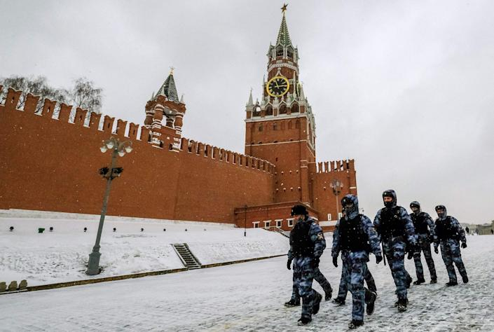 Police officers wearing protective face masks walk past the Spasskaya Tower of the Kremlin in Moscow on March 13, 2021 (AFP via Getty Images)