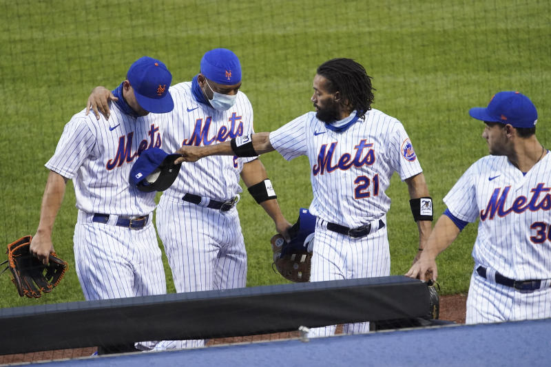 New York Mets third baseman J.D. Davis, left fielder Dominic Smith (2), center fielder Billy Hamilton (21), and right fielder Michael Conforto (30) walk off the field with teammates and the Miami Marlins before a baseball game Thursday, Aug. 27, 2020, in New York. The Mets and the Marlins jointly walked off the field after a moment of silence, draping a Black Lives Matter T-shirt across home plate as they chose not to start their scheduled game. (AP Photo/John Minchillo)