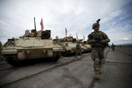 A member of the U.S. mechanized infantry company form 1st Brigade, 3rd Infantry Diivision walks past Bradley infantry fighting vehicles ahead an official opening ceremony of the joint U.S.-Georgian exercise Noble Partner 2015 at the Vaziani training area outside Tbilisi, Georgia, May 11, 2015. REUTERS/David Mdzinarishvili