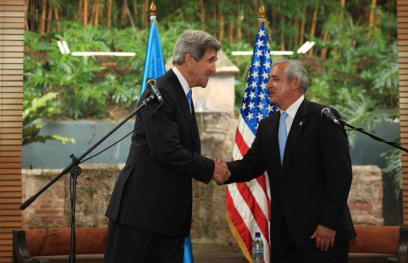 In this photo released by Guatemala's presidential press office, U.S. Secretary of State John Kerry, left, and Guatemala's President Otto Perez Molina shake hands during a meeting at the hotel Casa Santo Domingo in Antigua Guatemala, Tuesday, June 4, 2013. Kerry is in Guatemala for the annual general assembly of the Organization of American States (OAS). (AP Photo/Guatemala presidential press office)