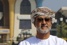 A man wearing a head scarf and sunglasses.