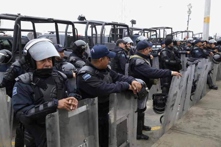 """Mexican Federal Police in riot gear guard outside of a migrant shelter for Central American immigrants in Piedras Negras, Mexico, Tuesday, Feb. 5, 2019. A caravan of about 1,600 Central American migrants camped Tuesday in the Mexican border city of Piedras Negras, just west of Eagle Pass, Texas. The governor of the northern state of Coahuila described the migrants as """"asylum seekers,"""" suggesting all had express intentions of surrendering to U.S. authorities. (Jerry Lara/The San Antonio Express-News via AP)"""