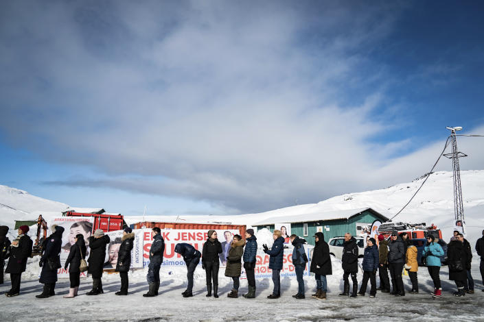 People queue to vote, in the Inussivik arena in Nuuk, Greenland, Tuesday April 6, 2021. Greenland is holding an early parliamentary election Tuesday focused in part on whether the semi-autonomous Danish territory should allow international companies to mine the sparsely populated Arctic island's substantial deposits of rare-earth metals. (Emil Helms/Ritzau Scanpix via AP)
