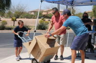 Dylan Pfeifer uses a lift to move a box filled with donated canned and boxed foods to his home in Chandler, Ariz., Saturday, April 3, 2021, to safely store the items until they are given to St. Mary's Food Bank. Pfeifer hosted his third food drive since October in response to the coronavirus pandemic. He collected about $450. (AP Photo/Cheyanne Mumphrey)