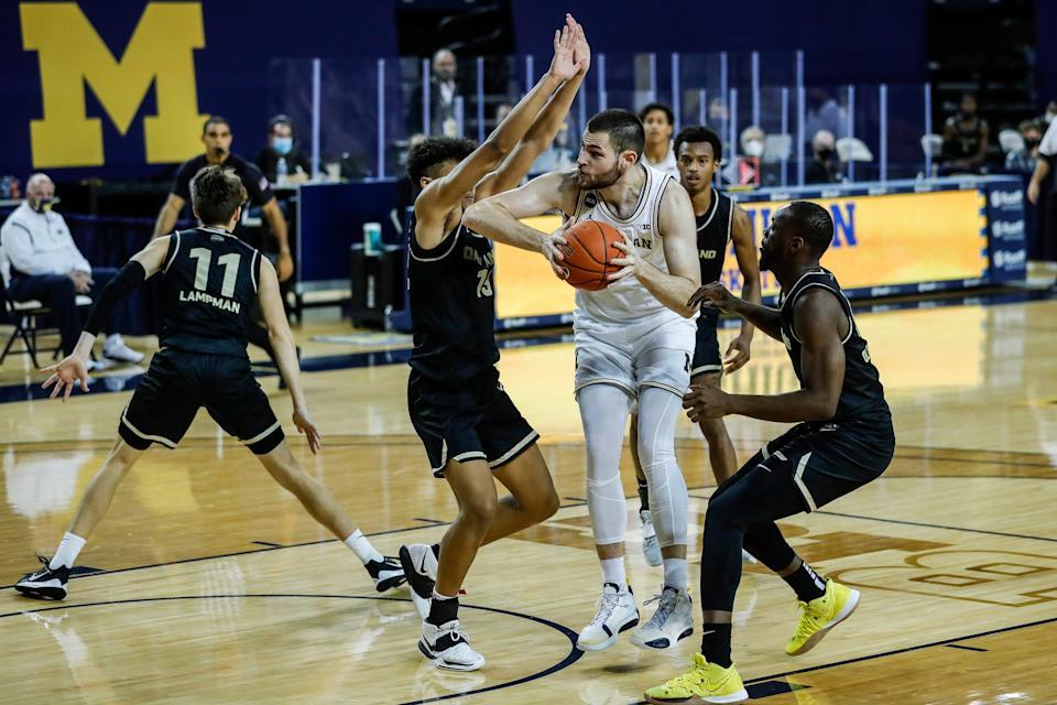 Michigan center Hunter Dickinson (1) makes a layup against Oakland forward Trey Townsend (13) during the overtime at the Crisler Center in Ann Arbor, Sunday, Nov. 29, 2020.