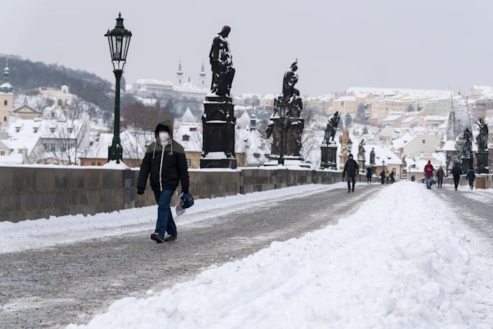 A woman wearing a facemask as a preventive measure against the spread of coronavirus, walks on the iconic Charles Bridge. Heavy snowfall across the Czech Republic has disrupted rail, road and public transport. (Photo by Tomas Tkacik / SOPA Images/Sipa USA)