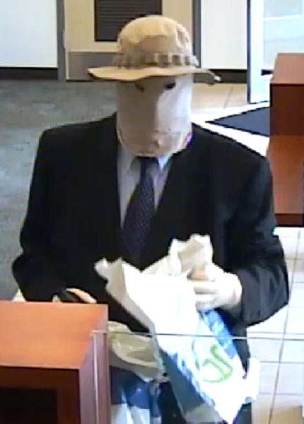 """This image made from a surveillance video provided by the FBI shows a disguised suspect robbing a PNC Bank on July 2, 2016, in North Wales, Pa. The FBI has arrested a suburban Philadelphia man it says was the """"Straw Hat Bandit,"""" a bank robber who wore a straw hat, mask and other disguises in stickups dating back to 2012. A federal indictment returned Wednesday, April 19, 2017, charged Richard Boyle, already a convicted bank robber, with carrying out 11 bank robberies that netted him nearly a half-million dollars. (FBI via AP)"""