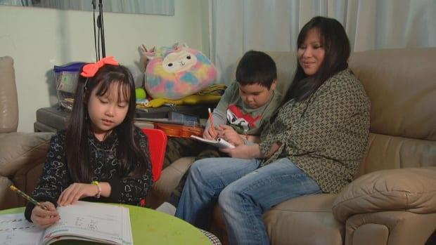 Kaye Banez supports her children Estelle and Lazarus as they work on their school assignments at home. (Gabriel Osorio/CBC News - image credit)