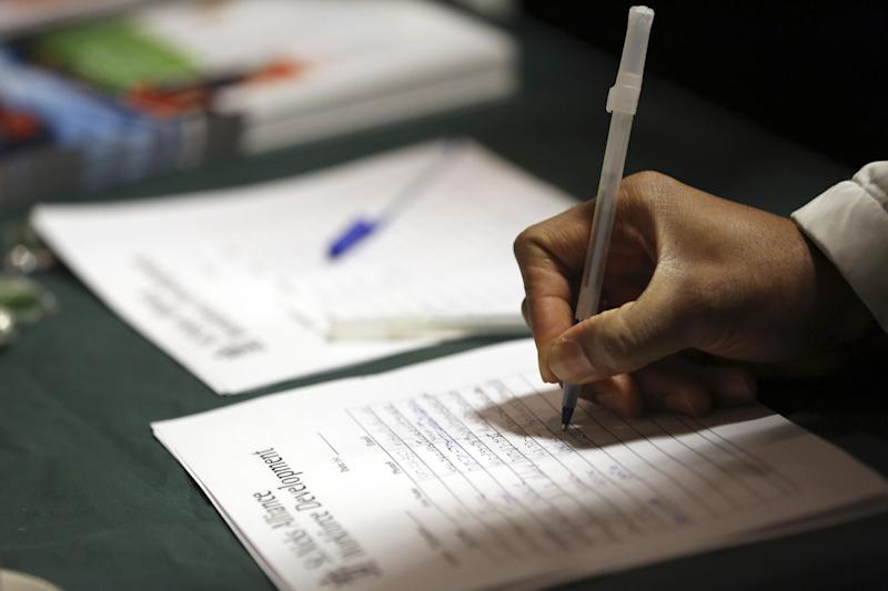 In this Wednesday, Dec. 12 2012 photo a job seeker leaves his contact information with a potential employer during a job fair in New York. More Americans sought unemployment benefits in the last week of 2012, though the winter holidays likely distorted the data for the second straight week. (AP Photo/Mary Altaffer)