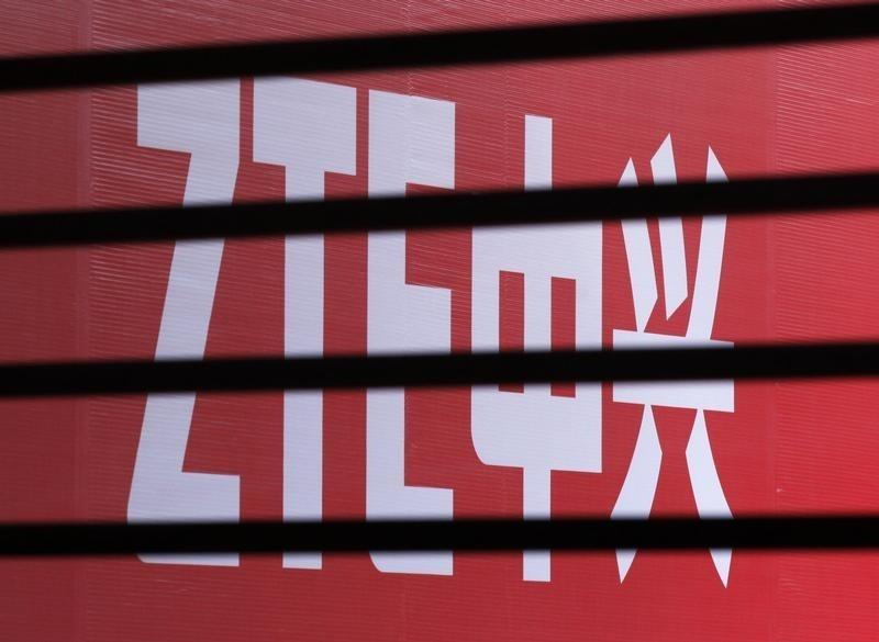 The company logo of ZTE is seen through a wooden fence on a glass door during the company's 15th anniversary celebration in Beijing
