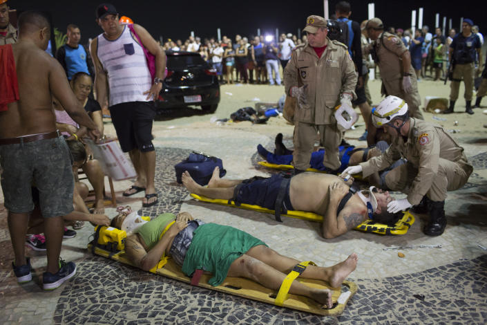 <p>Firefighters give the first aid to people that were hurt after a car drove into the crowded seaside boardwalk along Copacabana beach in Rio de Janeiro, Brazil, Thursday, Jan. 18, 2018. (Photo: Silvia Izquierdo/AP) </p>