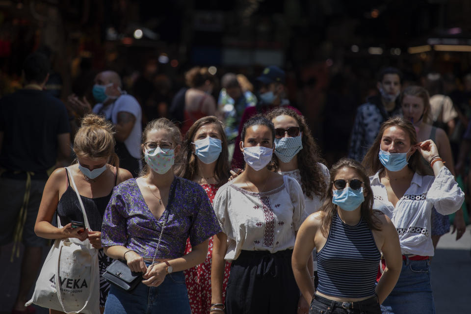 Tourists wearing face masks wait to cross a road in downtown Barcelona, Spain, Thursday, July 16, 2020. With Europe's summer vacation season kicking into high gear for millions weary of months of lockdown, scenes of drunken British and German tourists on Spain's Mallorca island ignoring social distancing rules and reports of American visitors flouting quarantine measures in Ireland are raising fears of a resurgence of infections in countries that have battled for months to flatten the COVID-19 curve. (AP Photo/Emilio Morenatti)