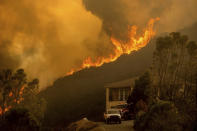 FILE - In this Monday, Aug. 17, 2020 file photo, flames from the River Fire crest a ridge in Salinas, Calif. In California, a Mediterranean climate sets up ideal conditions for fire then is worsened by climate change, says University of California, Merced, fire scientist LeRoy Westerling, who has had his home threatened twice in the last few years. (AP Photo/Noah Berger)