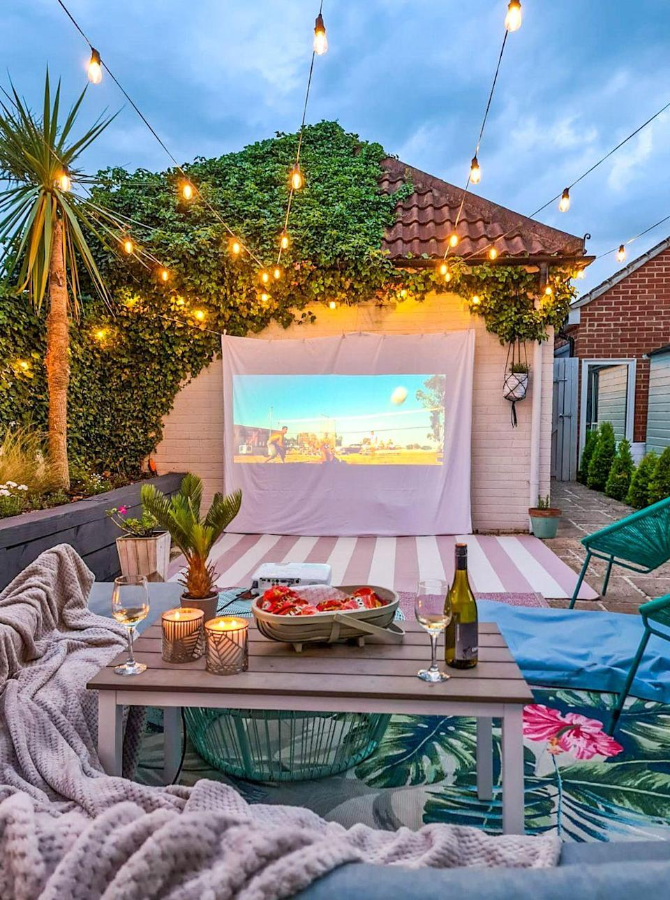 """<p>'To create the DIY Movie Night we used string, pegs and a kingsize white sheet to create the screen and a projector which we placed on a garden table and ran the leads underneath the seating to prevent hazards,' says Kel. </p><p><strong>READ MORE</strong>: <a href=""""https://www.housebeautiful.com/uk/garden/a32639929/outdoor-cinema/"""" rel=""""nofollow noopener"""" target=""""_blank"""" data-ylk=""""slk:How to create an outdoor cinema in your garden in 6 simple steps"""" class=""""link rapid-noclick-resp"""">How to create an outdoor cinema in your garden in 6 simple steps</a> </p>"""