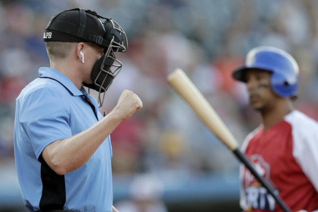 Home plate umpire Brian deBrauwere, left, calls a strike given to him by a radar system over an earpiece as Liberty Division's Tyler Ladendorf, right, of the High Point Rockers, strikes out to Freedom Division's Mitch Atkins, of the York Revolution, during the first inning of the Atlantic League All-Star minor league baseball game, Wednesday, July 10, 2019, in York, Pa. deBrauwere wore the earpiece connected to an iPhone in his ball bag which relayed ball and strike calls upon receiving it from a TrackMan computer system that uses Doppler radar. The independent Atlantic League became the first American professional baseball league to let the computer call balls and strikes during the all star game. (AP Photo/Julio Cortez)