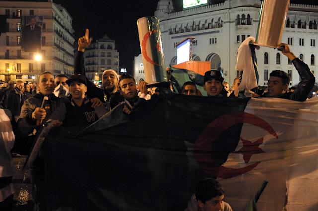 Algerian people hold an Algerian flag as they react after the World Cup qualifying playoff second leg soccer match against Burkina Faso, in Algiers, Tuesday, Nov. 19, 2013. Algeria won 1-0 to qualify for the 2014 World Cup in Brazil. (AP Photo/Sidali Djarboub)