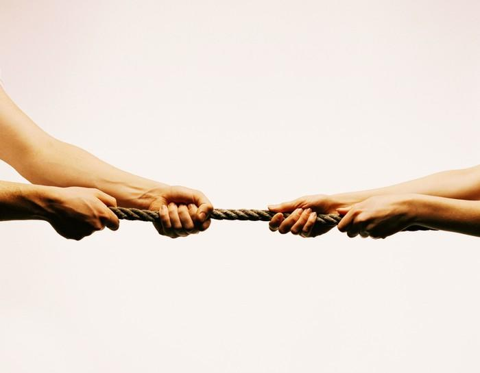 Two hands pulling on each side of a rope in a game of tug-of-war.