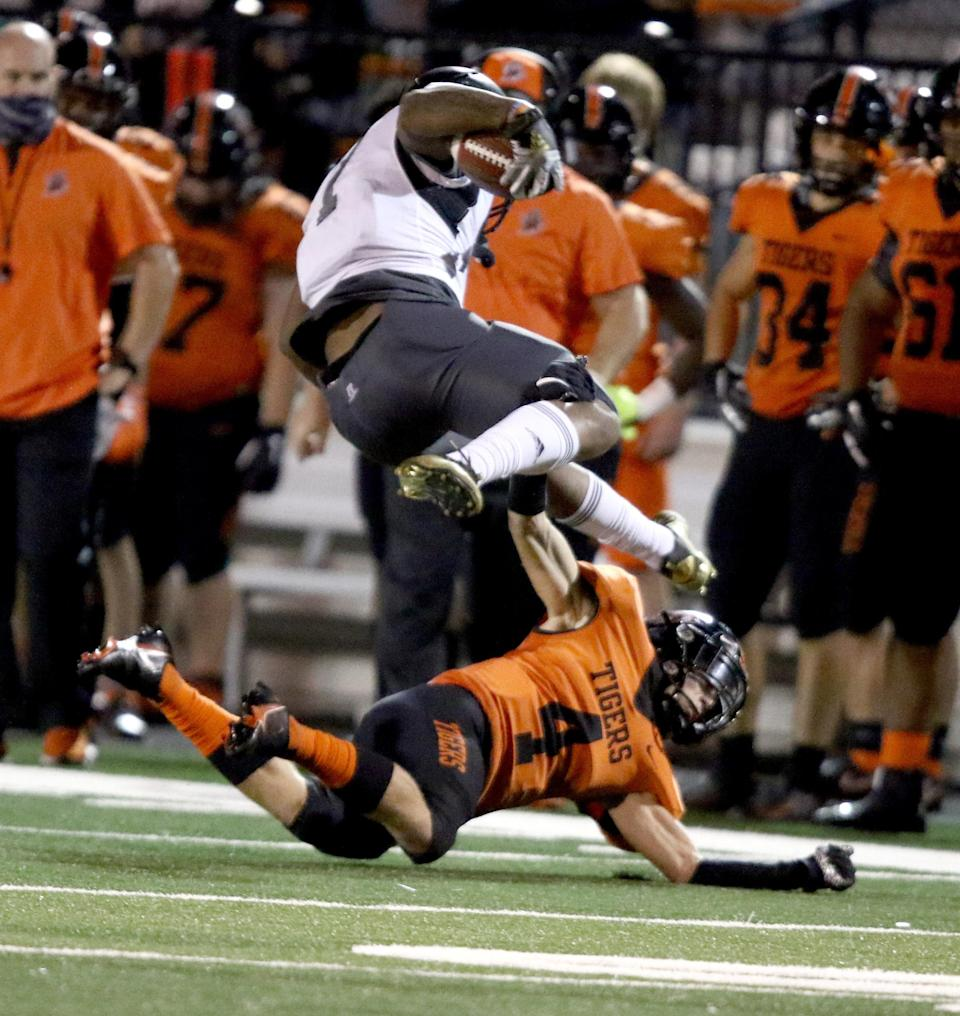 Massillon's Austin Brawley (4) takes out the legs of Bishop Sycamore's Daivon Lowman during a September 2020 game.