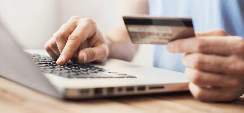 person holding credit card and typing on laptop computer