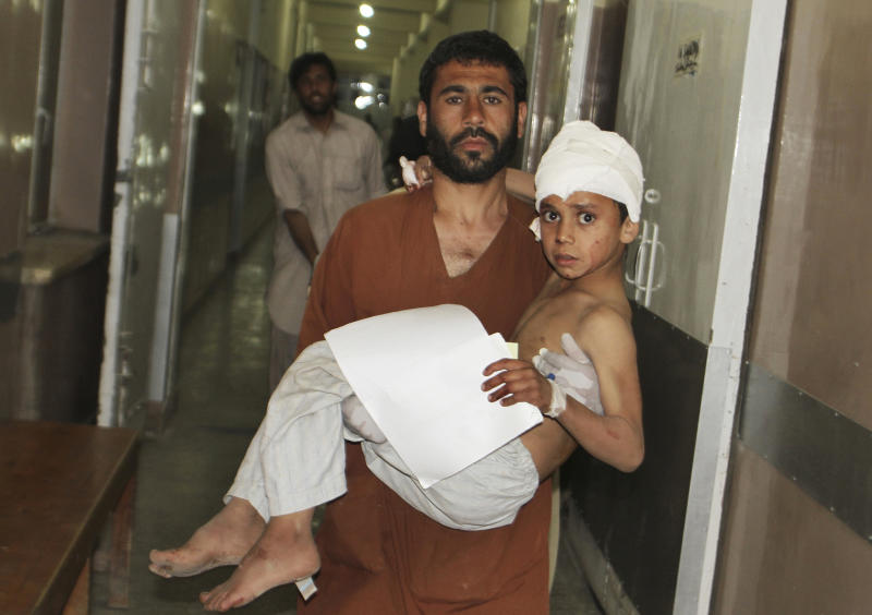 A young injured Afghan boy is carried by his father into the emergency room at the hospital in Kandahar, Afghanistan, Friday, May 17, 2013 after a car bomb exploded inside an elite gated community linked to the family of Afghan President Hamid Karzai. Many people where killed and scores wounded, an official said.(AP Photo/Allauddin Khan)