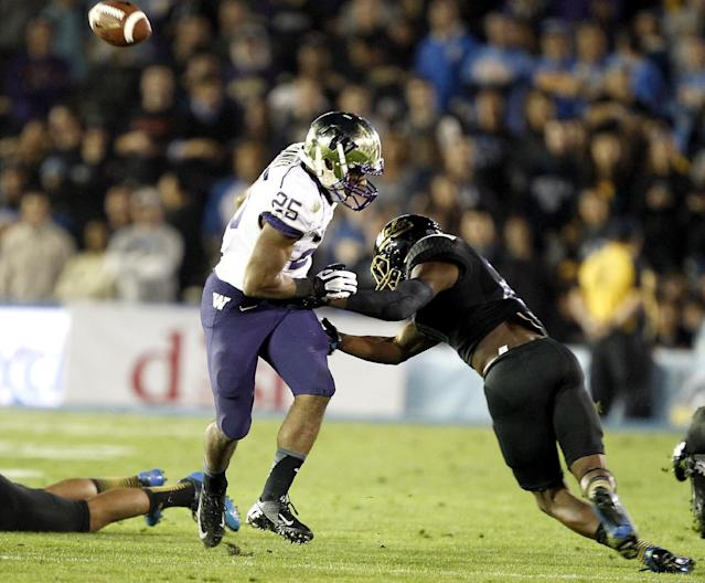 UCLA safety Tahaan Goodman, right, knocks the ball from Washington running back Bishop Sankey, left, on a run in the first quarter of their NCAA college football game Friday, Nov. 15, 2013, in Pasadena, Calif. UCLA recovered the fumble. (AP Photo/Alex Gallardo)