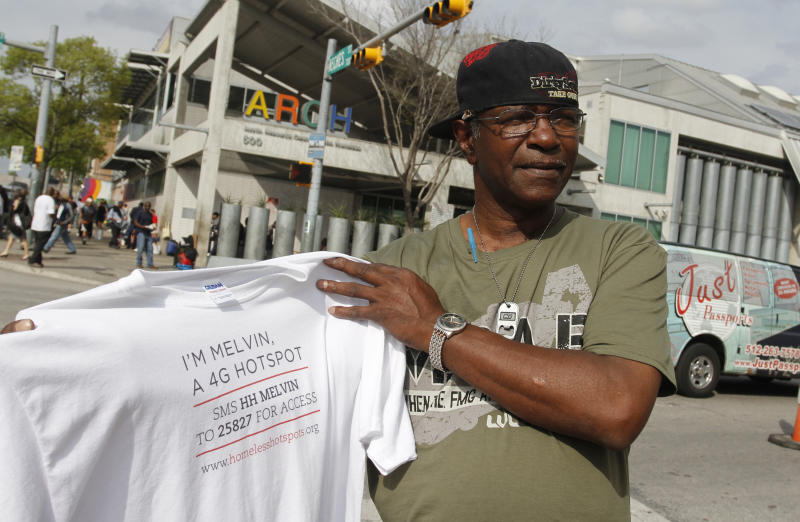 Melvin Hughes, a homeless man hired by BBH Labs to provide and promote a mobile 4G Wi-i service during SXSW, holds the T-shirt he was given by the marketing agency in Austin, Texas on Tuesday, March 13, 2012. Hughes said he was paid $20 for each six-hour shift over four days this past weekend and he may receive extra money if those who used the online 4G service made a donation.(AP Photo/Jack Plunkett)