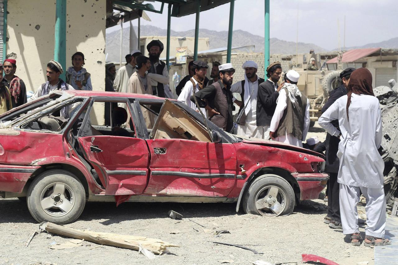 Villagers gather at the site of a car bomb attack in Urgon district, eastern province of Paktika July 15, 2014. A car packed with explosives exploded on Tuesday as it sped through a crowded market in Paktika, killing at least 89 people, officials said, one of the most violent attacks in the country in a year. REUTERS/Stringer (AFGHANISTAN - Tags: CIVIL UNREST)