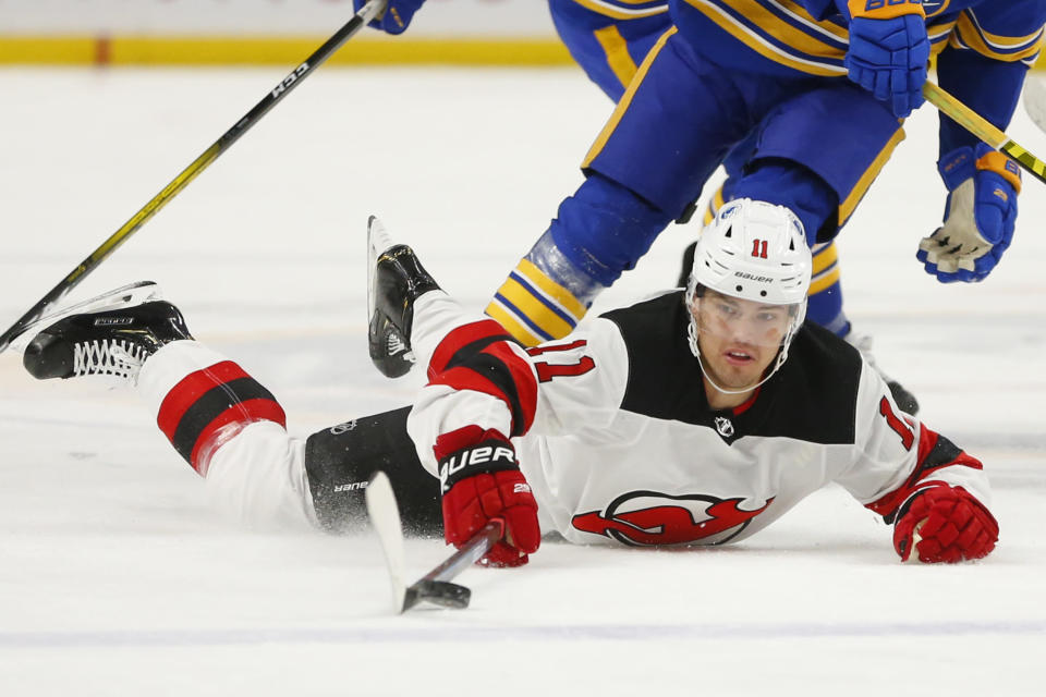 CORRECTS TO ANDREAS JOHNSSON INSTEAD OF WILL BUTCHER - New Jersey Devils forward Andreas Johnsson (11) is tripped during the first period of an NHL hockey game against the Buffalo Sabres, Sunday, Jan. 31, 2021, in Buffalo, N.Y. (AP Photo/Jeffrey T. Barnes)