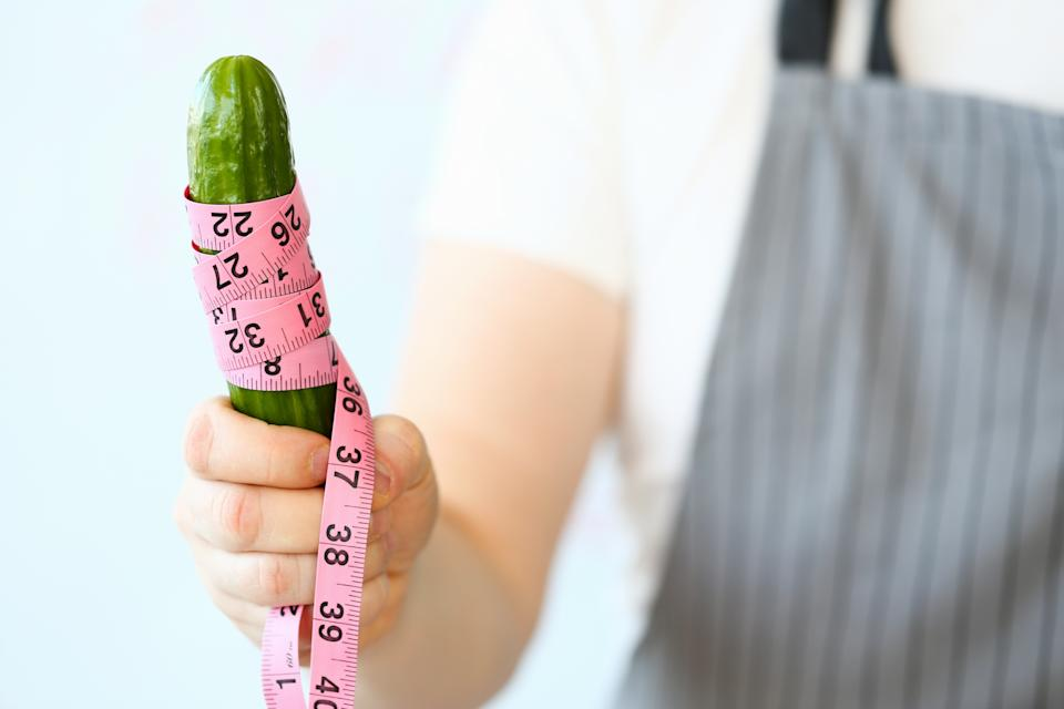 Abstract close-up woman hand diet concept with cucumber and measure tape. Female character with healthy and organic food. Sport nutrition for slim figure.