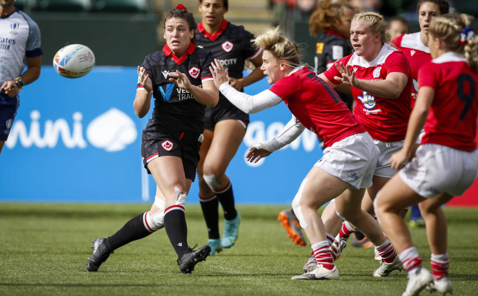 Canada's Alysha Corrigan, front left, passes the ball as Britain's Megan Jones grabs her during a women's HSBC Canada Sevens rugby match in Edmonton, Alberta, Saturday, Sept. 25, 2021. (Jeff McIntosh/The Canadian Press)