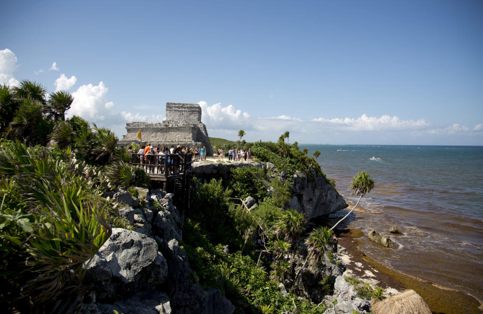 In this Aug. 5, 2018 photo, tourists vist the archeological site of Tulum on Mexico's Yucatan Peninsula. Almost seven million international tourists visit this stretch of coast every year; many of whom arrive at the Cancun airport and are bused or drive down the coast. (AP Photo/Eduardo Verdugo)