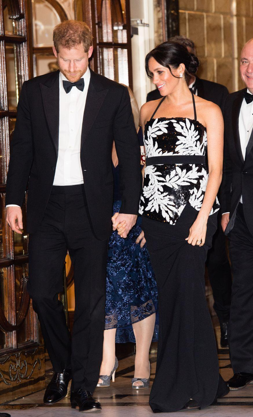 """<p>Arriving at the London Palladium, the pregnant royal looked sparkly in a £895 sequin halter-neck top with a leaf pattern and a £850 maxi skirt by London-based designer <a href=""""https://www.safiyaa.com/collections/tops/products/malaya-strapless-top"""" rel=""""nofollow noopener"""" target=""""_blank"""" data-ylk=""""slk:Safiyaa"""" class=""""link rapid-noclick-resp"""">Safiyaa</a>, whose clothing she first wore <a href=""""https://www.elle.com/uk/fashion/celebrity-style/a23813894/meghan-markle-prince-harry-royal-tour-style-outfits/"""" rel=""""nofollow noopener"""" target=""""_blank"""" data-ylk=""""slk:during her royal tour of Fiji last month"""" class=""""link rapid-noclick-resp"""">during her royal tour of Fiji last month</a>.</p><p>She teamed the look with a black and gold clutch bag, <a href=""""https://www.farfetch.com/uk/shopping/women/aquazzura-simply-irresistible-pumps-item-12141243.aspx?storeid=11146&size=26&pid=googleadwords_int&af_channel=Search&c=629762120&af_c_id=629762120&af_keywords=aud-301601826227%3Apla-383089413039&af_adset_id=52804059504&af_ad_id=218064673083&is_retargeting=true&shopping=yes&gclid=Cj0KCQiA_s7fBRDrARIsAGEvF8Qg63WdSbrlYG0AqwP-LgbYQpBffN-YMnO6vLsSrmyeL2NhnQMMsdcaAgPIEALw_wcB"""" rel=""""nofollow noopener"""" target=""""_blank"""" data-ylk=""""slk:black high-heeled Aquazzura pumps"""" class=""""link rapid-noclick-resp"""">black high-heeled Aquazzura pumps</a>, and <a href=""""https://www.maisonbirks.com/en/birks-snowflake-snowstorm-diamond-earrings-in-white-gold"""" rel=""""nofollow noopener"""" target=""""_blank"""" data-ylk=""""slk:Snowstorm earrings"""" class=""""link rapid-noclick-resp"""">Snowstorm earrings</a> from Canadian jewellery brand Birks.</p>"""