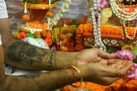 A fan with a tattoo of Amitabh Bachchan on his arm takes part in a ceremony praying for the Bollywood star's recovery from coronavirus in Kolkata