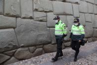 Police walk past the famous wall known as the stone with 12 angles, part of the current Religious Art Museum on Hatun Rumiyoc Street in Cusco Peru, Thursday, Oct. 29, 2020. All major sites around Cusco are currently open for free, in hopes of sparking any tourism after the COVID-19 pandemic brought it to a standstill. (AP Photo/Martin Mejia)