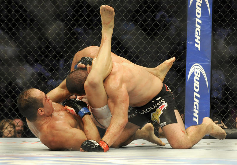Former heavyweight champion Junior Dos Santos, left, and UFC heavyweight champion Cain Velasquez fight for the UFC World Heavyweight title in Houston, Saturday, Oct. 19, 2013. Velasquez kept his title, beating Santos with a TKO in the fifth round. (AP Photo/Pat Sullivan)