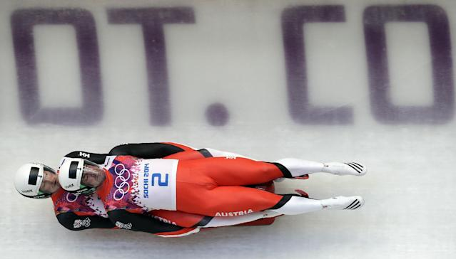 The doubles team of Andreas Linger and Wolfgang Linger from Austria speeds down the track in their first run during the men's doubles luge at the 2014 Winter Olympics, Wednesday, Feb. 12, 2014, in Krasnaya Polyana, Russia. (AP Photo/Michael Sohn)