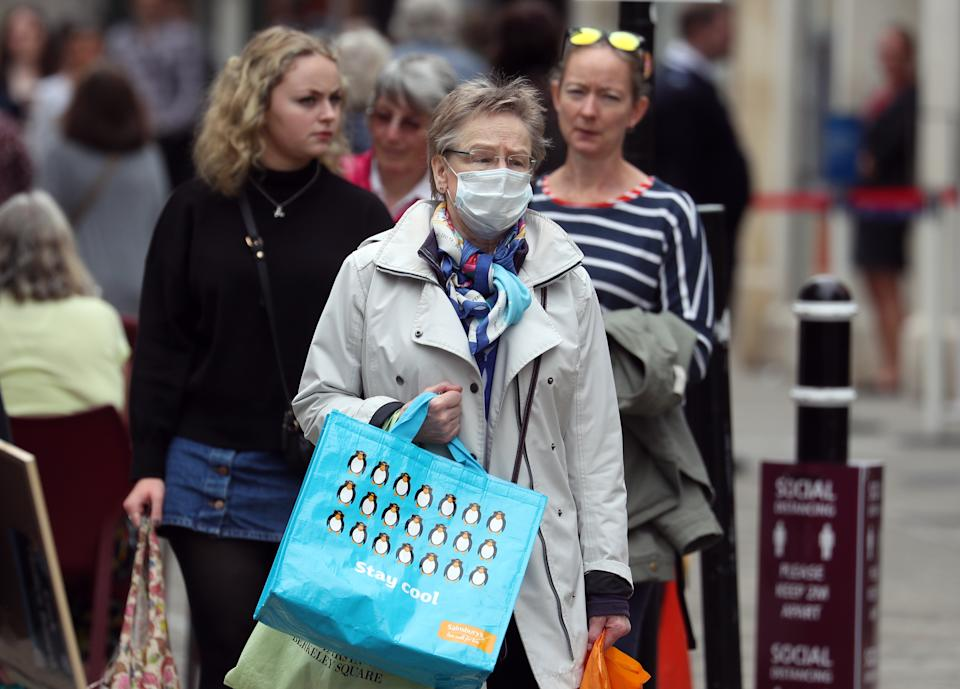 A person wears a face covering as they make their way along the High street in Winchester, Hampshire, after the lifting of further coronavirus lockdown restrictions in England.