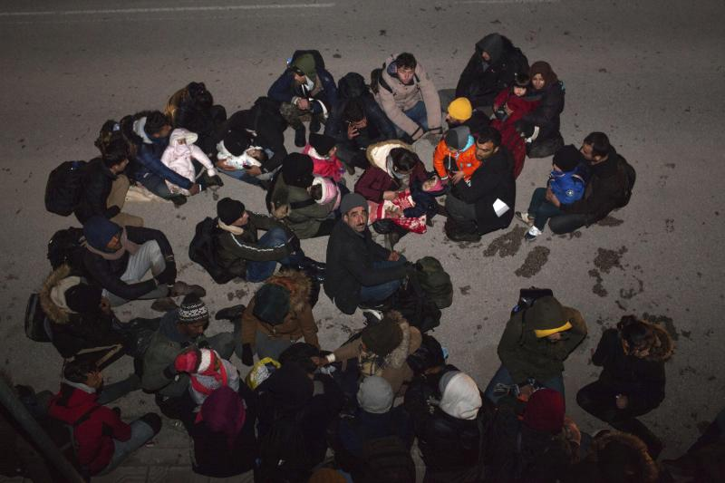 Migrants from Syria and Iraq wanting to register for asylum, sit on the road in Orestiada town, northeastern Greece, Monday, April 22, 2019. Greek authorities say dozens of asylum-seekers have turned up at the front door of European border agency employees helping police Greece's northeastern border with Turkey. (AP Photo/Antonis Pasvantis)