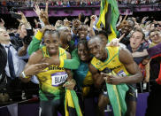 Jamaica's Usain Bolt, center right, celebrates winning gold in the men's 100-meter final with his mother Jennifer, center, and silver medallist Yohan Blake of Jamaica, center left, during the athletics in the Olympic Stadium at the 2012 Summer Olympics, London, Sunday, Aug. 5, 2012. (AP Photo/David J. Phillip )
