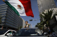 An anti-government demonstrator waves a Mexican flag as he rides out the sunroof of a car during a driving protest by hundreds of cars, calling for the resignation of President Andres Manuel Lopez Obrador, in Mexico City, Sunday, June 28, 2020. (AP Photo/Rebecca Blackwell)