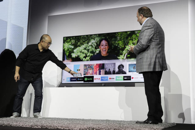 Samsung's Joseph Stinziano, right, watches as Yoon Lee demonstrates the SmartThings App during a news conference at CES International Monday, Jan. 8, 2018, in Las Vegas. (AP Photo/Jae C. Hong)