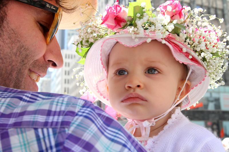 Secho Rodriguez, left, holds his 14 month old daughter Caetana Boente Rodriguez as they make their way along New York's Fifth Avenue during the Easter Parade, Sunday, April 20, 2014. (AP Photo/Tina Fineberg)