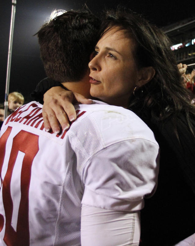 Alabama quarterback AJ McCarron (10)gets a hug from his mom, Dee Dee Bonner, after the second half of an NCAA college football game where Alabama defeated Mississippi State 20-7 on Saturday, Nov. 16, 2013, in Starkville, Miss. (AP Photo/Butch Dill)