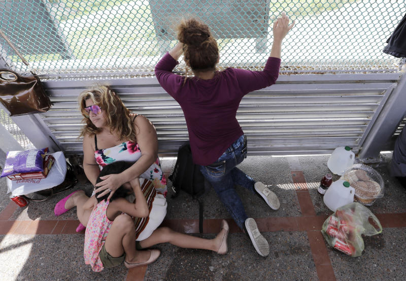 CORRECTS YEAR OF PHOTO TO 2018, NOT 2019 - FILE - In this June 24, 2018, file photo, immigrants from Honduras seeking asylum wait on the Gateway International Bridge, which connects the United States and Mexico, in Matamoros, Mexico. The Trump administration wants up to two years to find potentially thousands of children who were separated from their parents at the border before a judge halted the practice. The Justice Department said in a court filing late Friday, April 5, 2019, in San Diego that it will take at least a year to review the cases of 47,000 unaccompanied children taken in custody between July 1, 2017 and June 25, 2018. (AP Photo/David J. Phillip, File)