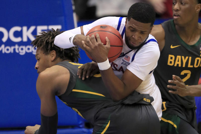 Kansas guard Isaiah Moss, top, rebounds on the back of Baylor forward Freddie Gillespie, left, during the first half of an NCAA college basketball game in Lawrence, Kan., Saturday, Jan. 11, 2020. (AP Photo/Orlin Wagner)