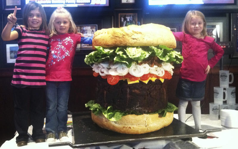 "In a Thursday, Oct. 20, 2011 photo provided by Mallie's Sports Grill in Southgate, Mich., children stand next to a 338-pound ""Absulutely Ridiculous Burger"" at the sports bar. The 3-foot-high sandwich packs 540,000 calories, takes 22 hours to cook and sells for $2000. Manager Jason Jones says it comes with fries and a drink. (AP Photo/Mallie's Sports Grill, Mike Matkin)  NO SALES"