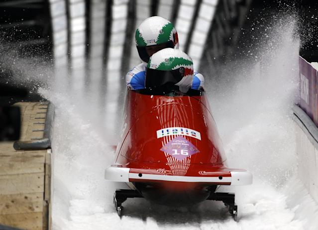 The team from Italy ITA-1, piloted by Simone Bertazzo and brakeman Simone Fontana, brake after their final run during the men's two-man bobsled competition at the 2014 Winter Olympics, Monday, Feb. 17, 2014, in Krasnaya Polyana, Russia. (AP Photo/Dita Alangkara)