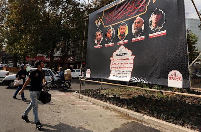 Iranians walk past a banner showing a portrait of Iran's Revolutionary Guards Brigadier General Hossein Hamedani (2nd R) and and two other comrades in Tehran on October 27, 2015 (AFP Photo/Atta Kenare)