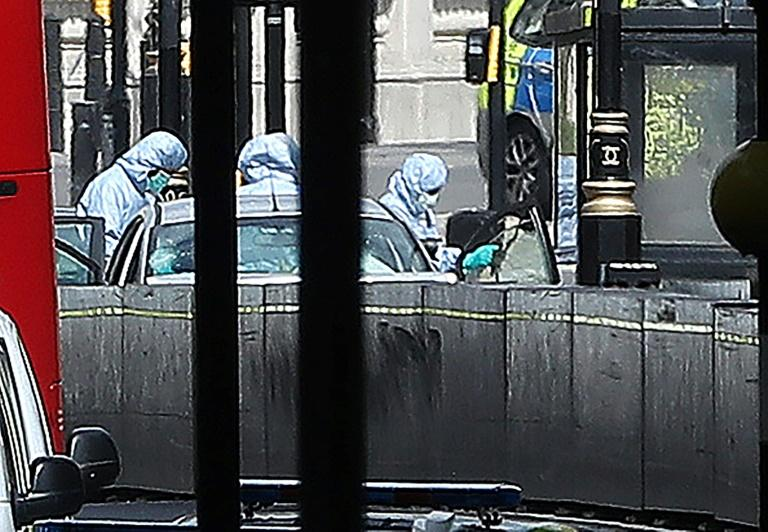 Police forensics officers inspect the car that crashed into a barrier outside Parliament in London